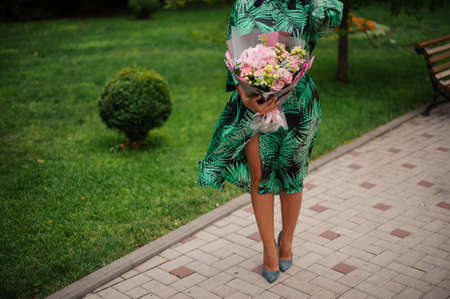 woman with bouquet of flowers walks in the park. Stock fotó - 147586165