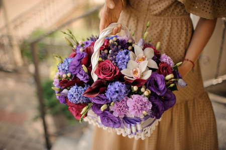 Beautiful white basket with flowers in purple tones in the hands of girl.