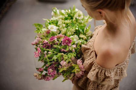 Top view of girl who holds bouquet in her hand.