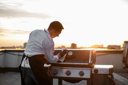 cook man wipes the grill equipment for barbecue Banque d'images
