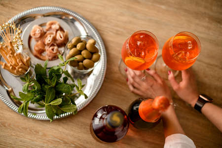 Top view on the table with glasses of cold bright orange drink which female hands hold