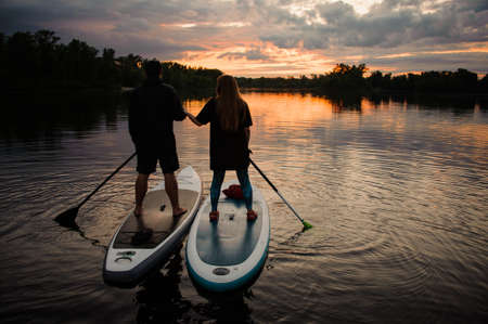 man and woman stand on sup boards and hold each others hands at sunset