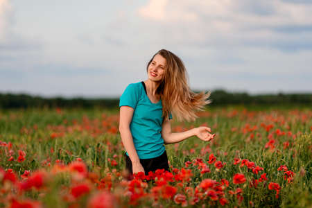 young smiling woman with long hair standing on field with red poppies.
