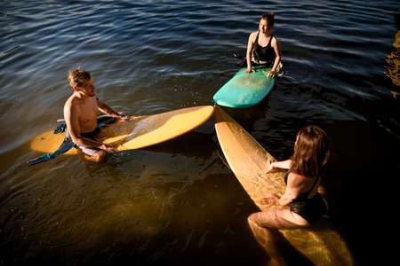 group of people sit on surf boards and get ready for swimming