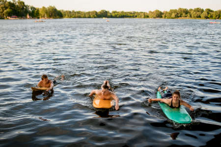 Front view of group of people which floating on surf boards on river water Banque d'images