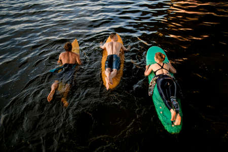 Top view of group of people which floating on surf boards on river water Banque d'images