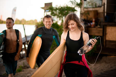 smiling woman and men with surfboards in their hands are walking near river