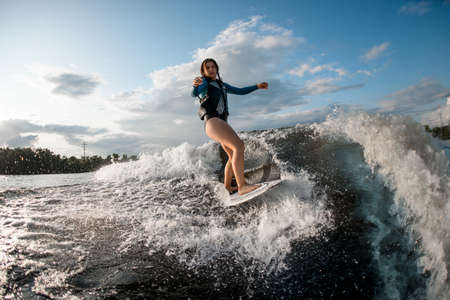 Active young woman wakesurfing down the river waves Stock Photo