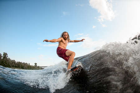young active man with dreadlocks ride the waves on surfboard. Stock Photo