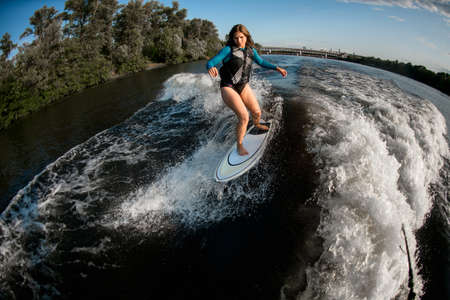 high angle view of young woman wakesurfing down the river waves Stock Photo