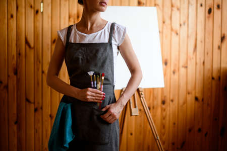 woman in gray apron holds several paint brushes in her hand