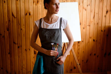 view on beautiful young woman artist in gray apron who stands and looks away