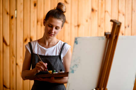 attractive woman with palette and brush in her hand and stands near easel and looks down