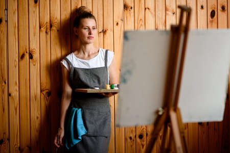woman with paints stands on wooden wall background and blurred easel in foreground.
