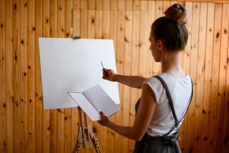 Young woman artist make sketch on canvas from book in her hand. Wall is sheathed with wooden boards in the background. 스톡 콘텐츠
