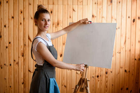 young woman artist stands near easel and holds the canvas with her hands and looks at the camera