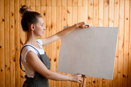 young woman artist stands in front of easel and holds the canvas with her hands and looks at it 스톡 콘텐츠