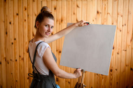 young smiling woman artist stands near easel and holds the canvas with her hands and looks at the camera