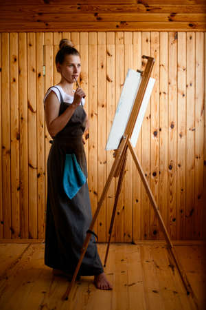 handsome young woman artist stands near an easel