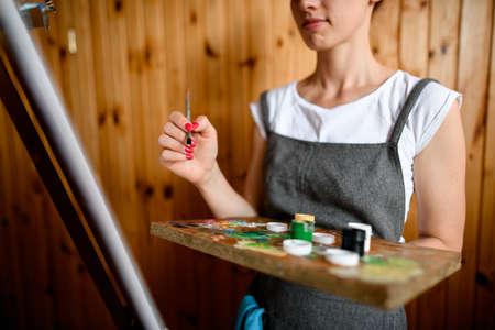 woman artist holds palette with multi-colored paints and brush and draws on canvas