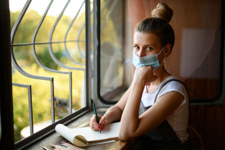 sad young woman in medical mask sits near window and looks at camera
