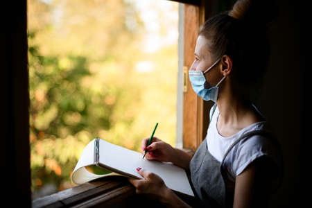 young woman inmedical mask stands near window with notebook and pencil. 版權商用圖片
