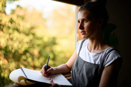 portrait of beautiful girl with paper notebook who stands near the window