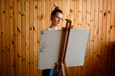Rear view of easel with canvas behind which is artist.