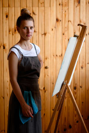 beautiful young woman artist stands opposite an easel