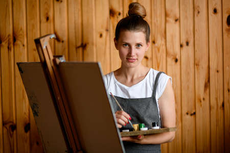 Beautiful young woman with palette and brush in her hand and stands near easel and looks at camera.