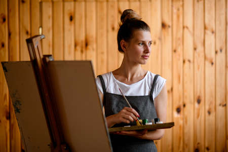 Pretty young woman with palette and brush in her hand and stands near easel and looks away