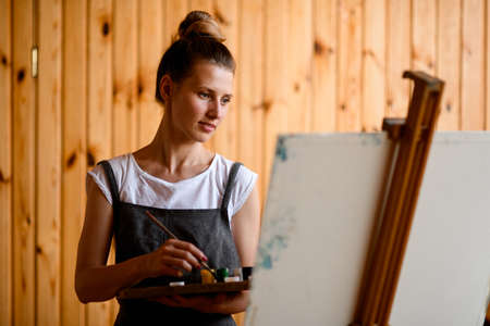 young female artist with palette and brush in her hand and stands near easel and looks at it