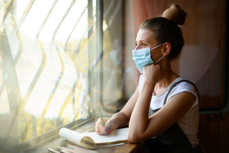 young woman in medical mask sits near window and looks out. 版權商用圖片