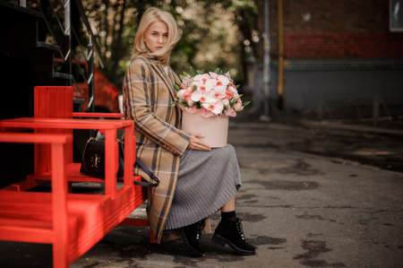 woman sitting on bench with flower arrangement on her lap and looks at camera. Archivio Fotografico
