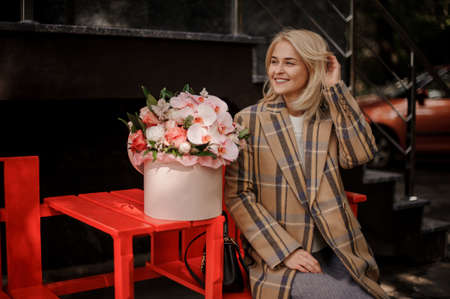 Cheerful blond woman sits on bench and next to her is box with flower arrangement Archivio Fotografico