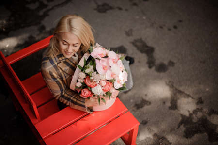 high angle view on woman which sits on bench with bouquet in her hands.