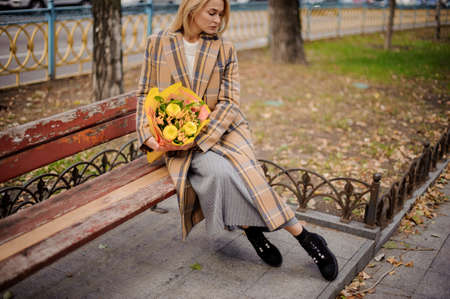 woman in plaid coat sits on bench with yellow bouquet of flowers in her hands.