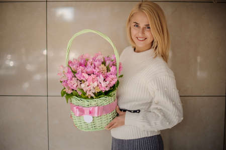 Beautiful young woman holds basket with pink ribbon and pink flowers inside and looking at camera.