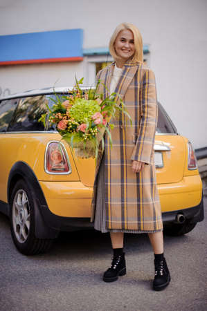 Smiling woman in coat stands with flower arrangement in her hand.