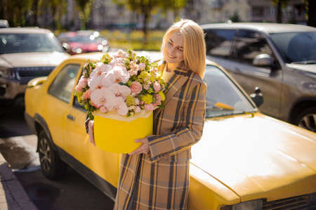Smiling woman in coat holds round yellow box with floral arrangement of roses and orchids