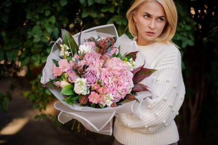 woman in white sweater holds large bouquet of different flowers and looks away.