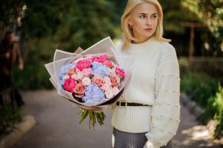 pretty woman holds large bouquet of different flowers and looks away.
