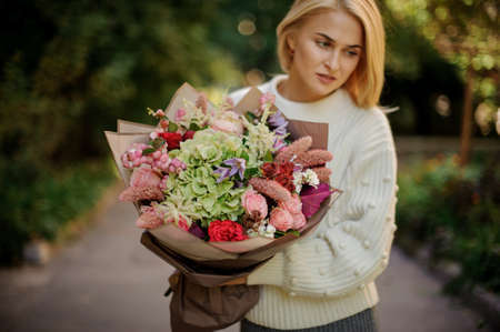 young woman holds large bouquet of different flowers and looks away.