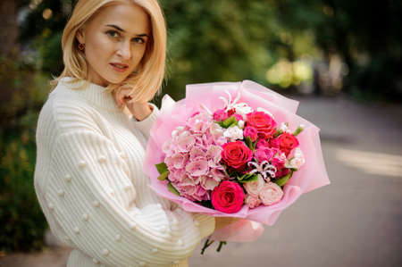 attractive young woman in her hands beautiful bouquet of flowers