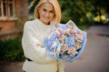 young smiling woman in her hands beautiful bouquet of flowers