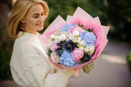 Cheerful woman holds bouquet of white, blue and pink flowers. 免版税图像
