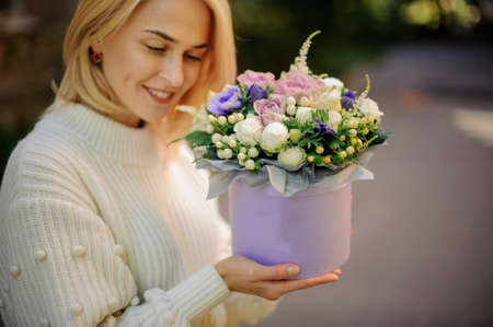 blonde woman holds round lilac box with flower arrangement inside it
