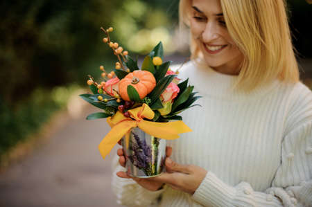 pot with composition of flowers of green leaves in hands of young smiling woman