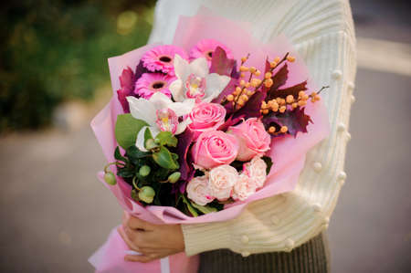 Close-up of bouquet with roses, gerbera, orchids and berries in the hands of woman.