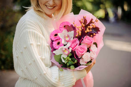 Beautiful bouquet of roses, gerbera, orchids and berries in the hands of woman. 免版税图像